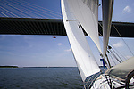 Sailboat Sailing Sails Arthur Ravenel Jr Bridge over Cooper River Charleston SC with Coast Guard Dolphin Helicopter