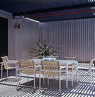 This contemporary al-fresco dining area is enclosed by corrugated metal walls and a slatted roof