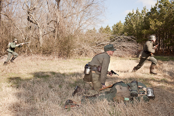 February 18, 2012. Enfield, NC.. A German medic tends to a wounded comrade as other soldiers form the 208 Infantry Regiment attack an American position.. Reenactors depict German infantry units in a reenactment of the Battle of the Rhineland, which took place September 15, 1944- March 21, 1945..