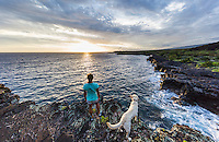 A woman and her dog hiking the historic 1871 Trail pause to take in the sunset in Honanau, Big Island. The ancient trail was the main artery for coastal travel between several villages in the area.