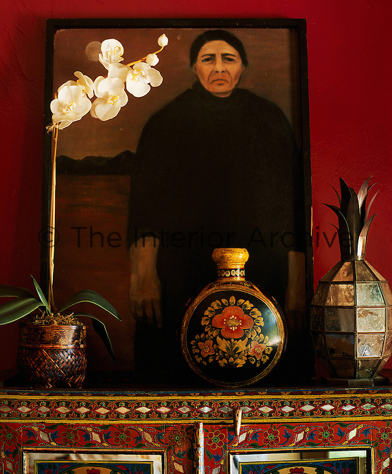 On top of an intricately inlaid cupboard in the dining room an orchid is arranged next to a sombre portrait propped against the deep red walls