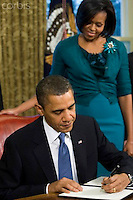 09 Feb 2010, Washington, DC, USA --- US President Barack Obama speaks before signing a memorandum on childhood obesity as First Lady Michelle Obama looks in the Oval Office of the White House in Washington, DC      --- Image by © Brooks Kraft/Corbis