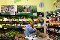 """Nick Jenkins stocks produce at the Durham Co-op Market Grocery and Cafe. He says he's lived Durham's West End for about 20 years, first on Wilkerson Street and now on Burch Avenue. He says he has seen the the neighborhood change, and the development has made it """"more peaceful."""" Shot in Durham, N.C. on Thursday, March 26, 2015. (Justin Cook)"""