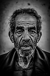 A portrait of an elderly man with wrinkled face and upset look. Photo by Sanad Ltefa