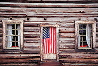 AN AMERICAN FLAG HANGS IN THE DOORWAY OF A HISTORIC LOG CABIN AT THE LANGLADE COUNTY HISTORICAL MUSEUM IN ANTIGO WISCONSIN.