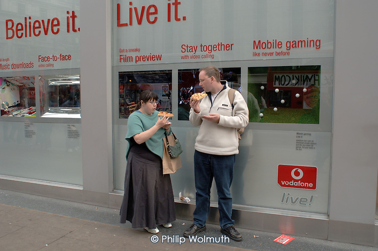 Tourists eat pizza outside the Vodafone store in Oxford Street, London.