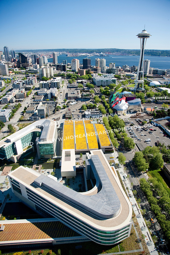 An aerial view of the Bill & Melinda Gates Foundation campus with the Seattle skyline, the Space Needle, and Puget Sound in the background.