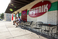 Couple enjoys a cold beer on a hot day as summer heat wave temperatures boil over 100 in East Austin's East 6th Street.