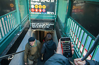 A subway rider checks the new MTA Subway Time app outside the Times Square station in New York on Friday, December 28, 2012, the day that the app has been released. Using the technology that is the engine behind the widely popular MTA countdown clocks in stations, the app, available only for iOS right now, provides real-time arrival data so you know when your next train arrives. The app only works with the MTA numbered lines at this time. (© Richard B. Levine)