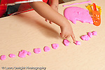 Education preschool 3-4 year olds art activity play dough closeup of girl's hand pointing at pieces of play dough as she counts them vertical