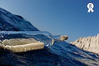 Bottle containing message floating in sea, close-up (Licence this image exclusively with Getty: http://www.gettyimages.com/detail/sb10065474e-001 )