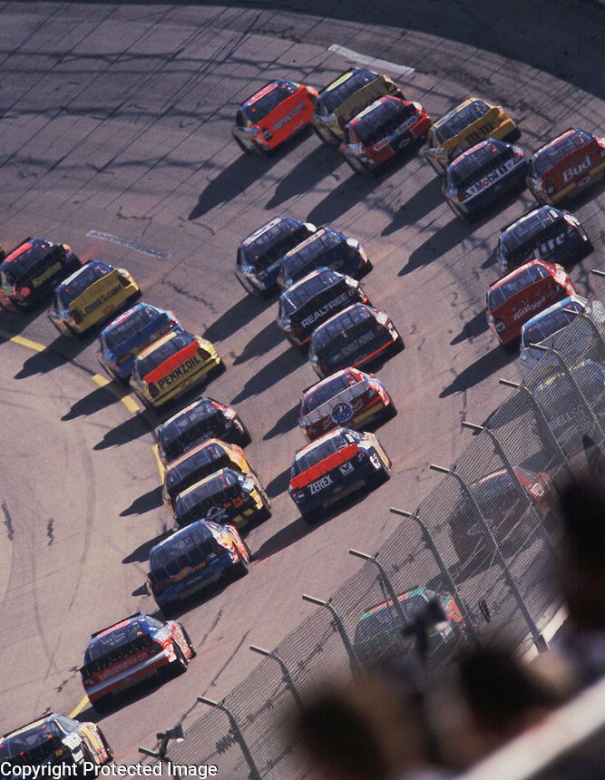 A pack of cars races into the first turn during  the Winston 500 at Talladega, AL in October 2000. (Photo by Brian Cleary)