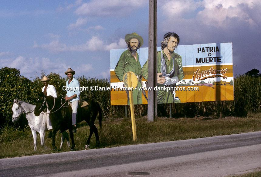 "In central Cuba two horseback riders pass a billboard showing revolutionary heroes Camilo Cienfuegos and Ernesto ""Che"" Guevara in 1999."