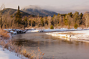 Swift River during the winter months in Albany, New Hampshire USA. This river travels along side of the Kancamagus Scenic Byway, which is one of New England's scenic byways. Mount Passaconaway is off in the distance.