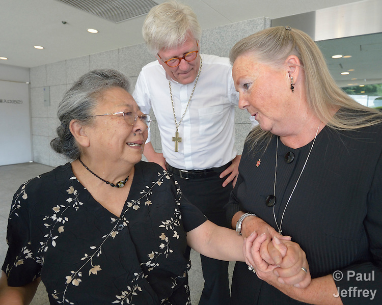 Koko Kondo (left), a survivor of the 1945 atom bombing of Hiroshima, Japan, talks with Bishop Mary Ann Swenson (right) and Bishop Heinrich Bedford-Strohm (center). Swenson, a United Methodist from the U.S., is vice moderator of the World Council of Churches Central Committee, and Bedford-Strohm is chair of the Evangelical Church in Germany (EKD). Swenson and Bedford-Strohm came to Hiroshima in August 2015 as part of a delegation of church leaders representing the World Council of Churches. They came to see for themselves the suffering caused by the bomb, to listen to the survivors and local church leaders, and to return home recommitted to advocating for an end to nuclear weapons. Kondo is a well-known hibakusha, or atom bomb survivor, who along with her father is mentioned in John Hershey's landmark book about the horror of Hiroshima.