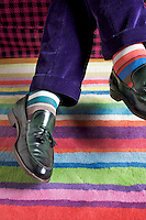 Paolo Bagnara wears socks which co-ordinate with the colourful stripes of the rug in his study