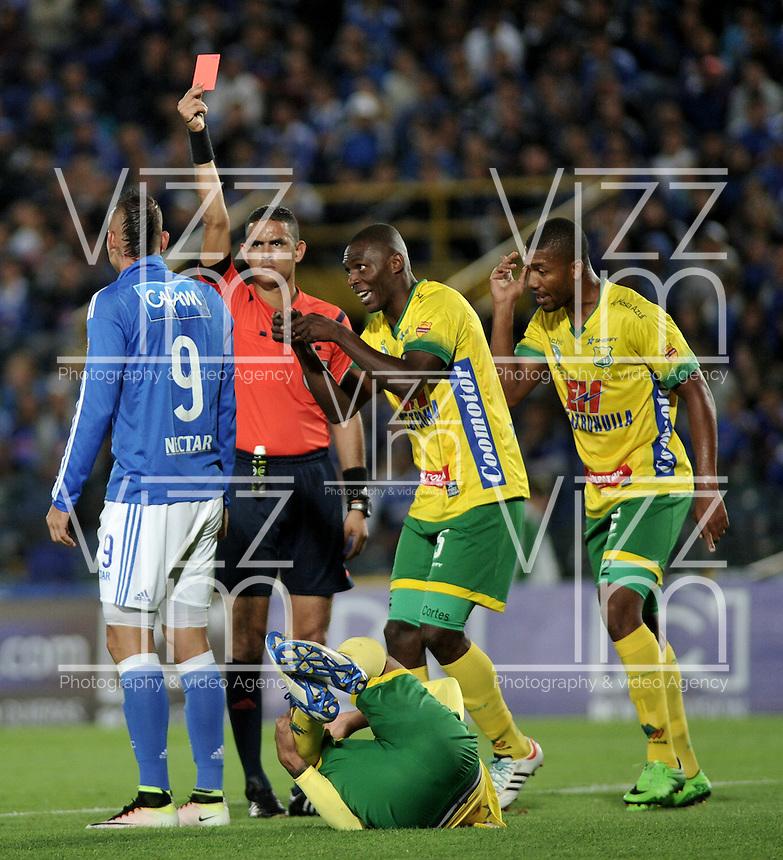 BOGOTA - COLOMBIA - 21 - 05 - 2016: Carlos Ortega (Cent), arbitro, muestra tarjeta roja a Michael Rangel (Izq.) jugador de Atletico Huila, durante partido de la fecha 19 entre Millonarios y Atletico Huila, de la Liga Aguila I-2016, jugado en el estadio Nemesio Camacho El Campin de la ciudad de Bogota.  / Carlos Ortega (C), referee, shows yellow card to Michael Rangel (L), player of Atletico Huila, during a match between Millonarios and Atletico Huila, for the date 19 of the Liga Aguila I-2016 at the Nemesio Camacho El Campin Stadium in Bogota city, Photo: VizzorImage / Luis Ramirez / Staff.