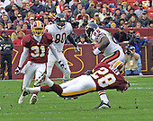 Landover, MD - December 23, 2001 -- Washington Redskin defensive back Darrell Green (28) tackles Chicago Bear wide receiver Marty Booker (86) during the game at FedEx Field in Landover, Maryland on December 23, 2001.  Also pictured are Bears wide receiver Dez White (80) and Redskins defensive back David Terrell (31). The Redskins lost the game 20 - 15.<br /> Credit: Arnie Sachs / CNP