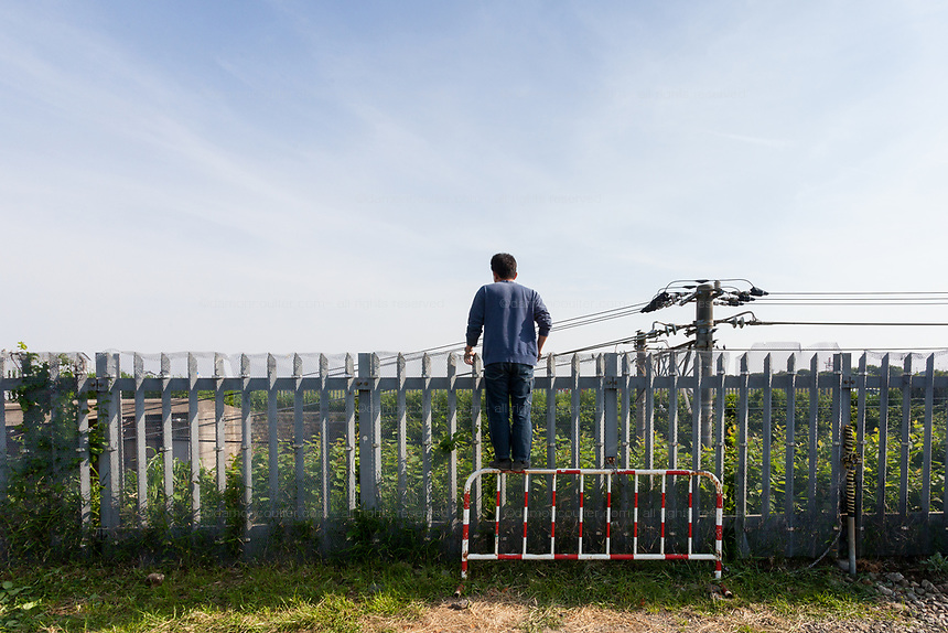 A man climbs on a barrier to look over a fence into Atsugi Airbase and watch the military aircraft. Yamato, Kanagawa, Japan. Tuesday May 1st 2018