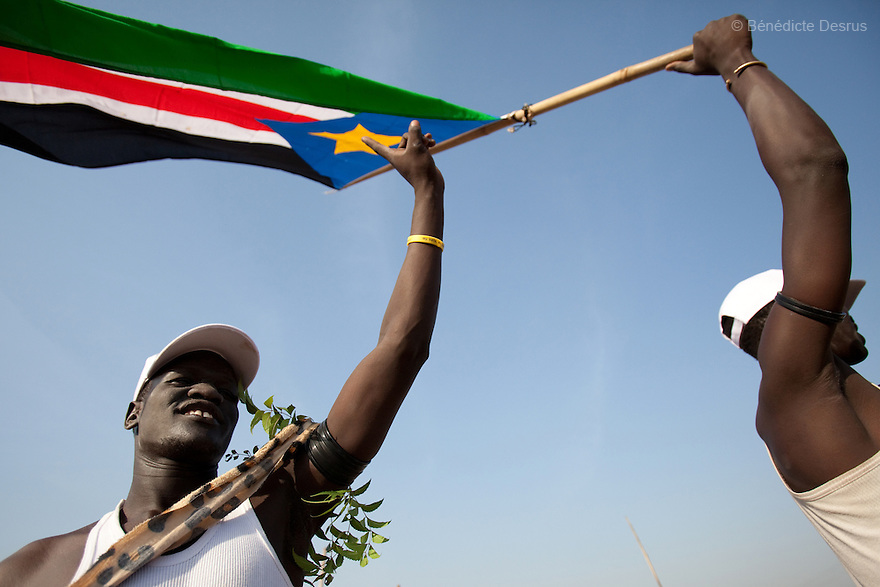 Sunday 9 january 2011 - Juba, Sudan - Southern Sudaneses wave a South Sudan flag during the referendum at the John Garang memorial mausoleum where a polling station is being set up in Juba. About four million Southern Sudanese voters began casting their ballots Sunday in a weeklong referendum on independence that is expected to split Africa's largest nation in two. Photo credit: Benedicte Desrus