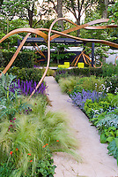 Garden sculpture artwork with gazebo, ornamental grass perennials, spiky plants, mix of textures. Steam bent oak freeform sculpture of wood. Garden design by Andy Sturgeon for Cancer Research, Chelsea Flower Show 2007. Gold Medal winner.