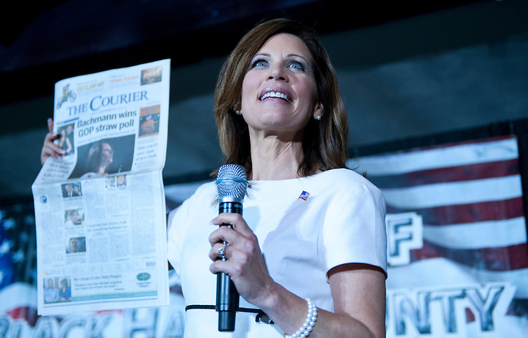 UNITED STATES - AUGUST 14:  Republican presidential candidate Rep. Michele Bachmann, R-Minn., holds up the Waterloo-Cedar Falls Courier during the Lincoln Day Dinner hosted by the Black Hawk County Republican Party in Waterloo, Iowa.  Candidates Bachmann, Rick Santorum, and Texas Gov. Rick Perry, addressed the gathering.  (Photo By Tom Williams/Roll Call)