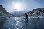 Snow Leopard (Panthera uncia) biologist, Shannon Kachel, crossing river in mountain valley, Sarychat-Ertash Strict Nature Reserve, Tien Shan Mountains, eastern Kyrgyzstan