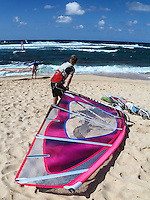 A windsurfer pulls his windsurfing board closer to the ocean while waiting his turn at Ho'okipa Beach, Maui. (NOTE: the man in foreground model released, the others are not model released.)