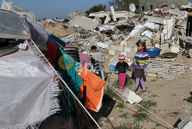 Palestinian children play outside their tents donated by a charity organisation as temporary housing for those whose houses were destroyed during a seven-week Israeli offensive, in Khuzaa, east of Khan Younis, in the southern Gaza Strip, on March 01, 2015. Photo by Abed Rahim Khatib