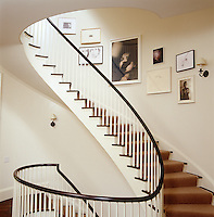 The walls on this curved staircase are used to display a collection of photographs and drawings