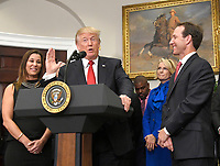 United States President Donald J. Trump makes remarks prior to signing an Executive Order to promote healthcare choice and competition as Leslie Baudry, Baudry Therapy, left, and Rich Baudry, Baudry Therapy Center and BRIO, right, look on in the Roosevelt Room of the White House in Washington, DC on Thursday, October 12, 2017.  The President's controversial plan is designed to make lower-premium health insurance plans more widely available.<br /> Credit: Ron Sachs / Pool via CNP<br /> <br /> Rich Baudry, Baudry Therapy Center and BRIO and /MediaPunch