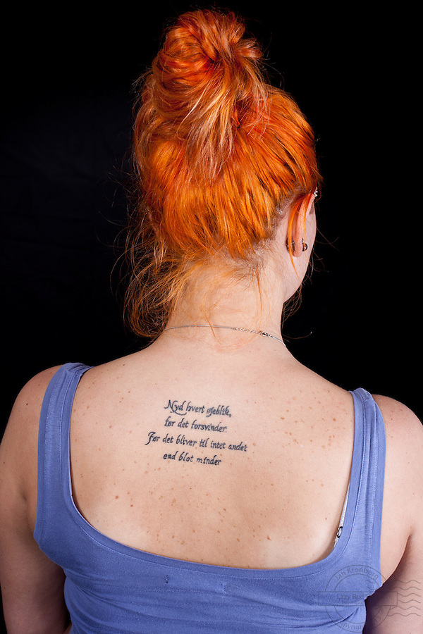 Young danish woman with danish &quot;carpe diem&quot; poem tattooed on upper back.<br />