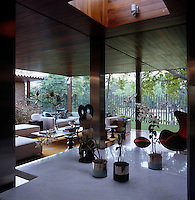 View over a low marble-topped table with orchids towards the open-plan living area surrounded by glass walls