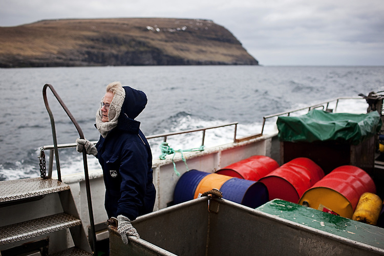 A woman rides a ferry to the village of Svínoy in the Faroe Islands.