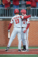 Heston Kjerstad (18) of the Arkansas Razorbacks is greeted at home plate by teammate Jordan McFarland (13) following his 2-run home run against the Charlotte 49ers at Hayes Stadium on March 21, 2018 in Charlotte, North Carolina.  The 49ers defeated the Razorbacks 6-3.  (Brian Westerholt/Four Seam Images)