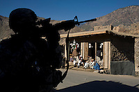 A soldier from Charlie Company, 3rd Platoon uses his telescopic sights as he provides security for a local English school graduation ceremony in Nanglam village in the Pesh Valley. The unit was providing security for the English school graduation ceremony in an effort to maintain support from the local community and stabilise the security in this pro-Taliban region, which sees some of the heaviest fighting in Afghanistan.