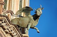 Bronze statue of a winged ox representing the the Evangelist Luke created by Maitani and collaborators between 1325 and 1330 on the14th century Tuscan Gothic style facade of the Cathedral of Orvieto, designed by Maitani, Umbria, Italy