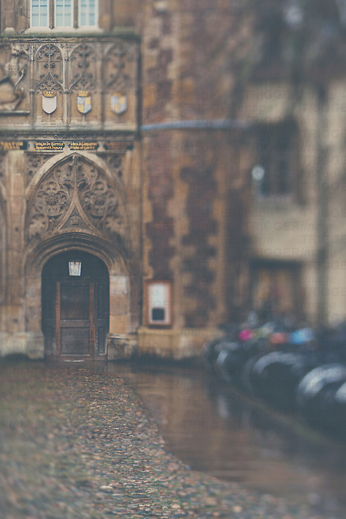 the door to St Johns College, Cambridge with bicycles lined up outside on a wet English afternoon.