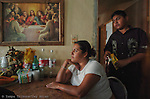 Norma Rodriguez, 30, sits at the table and talks about her immigration troubles as Jose Lamas, 14, stands behind her. The home in Matamoros Mexico was the setting for a family gathering after a funeral the day before.