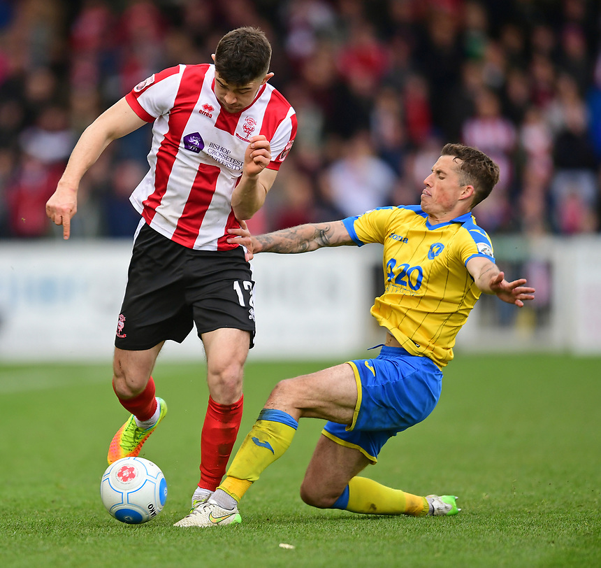 Lincoln City's Sean Long is tackled by Torquay United's Damon Lathrope<br /> <br /> Photographer Chris Vaughan/CameraSport<br /> <br /> Vanarama National League - Lincoln City v Torquay United - Friday 14th April 2016  - Sincil Bank - Lincoln<br /> <br /> World Copyright &copy; 2017 CameraSport. All rights reserved. 43 Linden Ave. Countesthorpe. Leicester. England. LE8 5PG - Tel: +44 (0) 116 277 4147 - admin@camerasport.com - www.camerasport.com