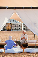 Two people sit sharing tea in the shade of the tented sitting area at the centre of the desert camp