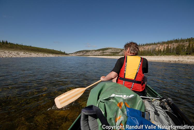 Mann padler kano en varm sommerdag. ---- Man canoeing a summer day.