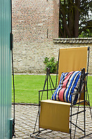 An antique metal and canvas garden chair on the cobbled path of the courtyard