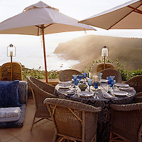 Cane chairs and parasols surround a table laid for lunch on the terrace overlooking the Indian Ocean