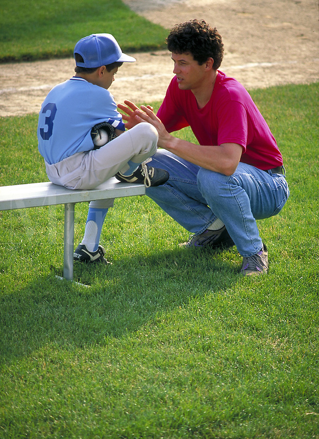 Little League player gets advice from coach