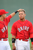 Shortstop Mauricio Dubon (10) of the Greenville Drive, left, admires the new hair style of second baseman Yoan Moncada (24) before a game against the Augusta GreenJackets on Thursday, June 11, 2015, at Fluor Field at the West End in Greenville, South Carolina. The Cuban-born 19-year-old Red Sox signee has been ranked the No. 1 international prospect in baseball by Baseball America. Greenville won, 10-1. (Tom Priddy/Four Seam Images)