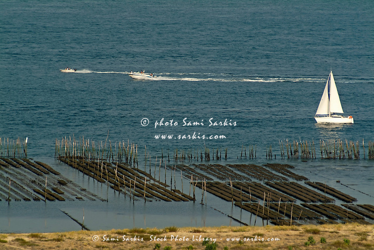 Boats sailing past an oyster farm in Archachon Bay, Gironde, France.