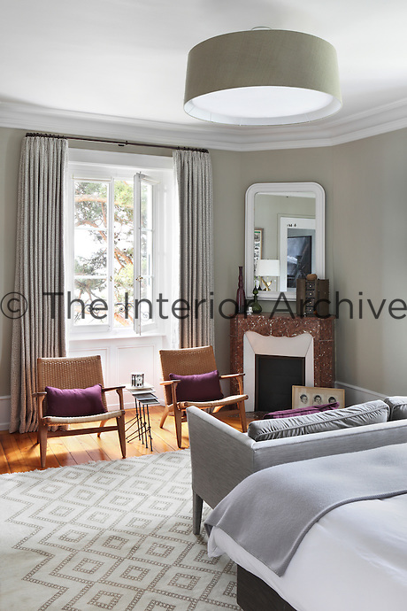 Varnished wood floors, woven chairs and burgundy cushions bring warmer tones into this stylish grey and white bedroom