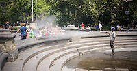A NYC Dept. of Parks worker sprays hot passer-by on request as he cleans the fountain in Washington Square Park, temporarily shut down for maintenance, on Friday, July 19, 2013. The fountain is normally filled with hot New Yorkers and visitors seeking a respite from the heat. The heat wave the city is experiencing is into its fifth day with temperatures in the high 90's with the heat index, a amalgam of heat and humidity,  poised to reach 105 degrees.  ( © Richard B. Levine)