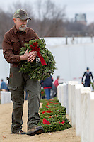 NWA Media/JASON IVESTER --12/13/2014--<br /> U.S. Naval veteran Curtis Cross of Bella Vista places wreaths at headstones on Saturday, Dec. 13, 2014, following the Wreaths Across America ceremony at the Fayetteville National Cemetery. Wreaths were placed at each of the 7100 veteran graves in the cemetery.